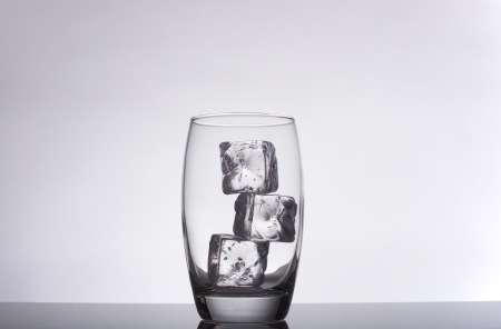 glass with ice cubes on a gradient