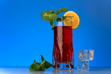 a fresh currants flavored drink with mint and orange on blue