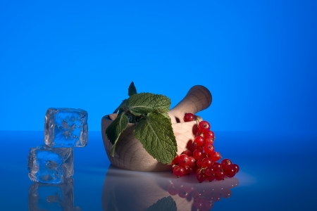 mortar and pestle with mint, currants and ice on blue spot lighting Stock Photo