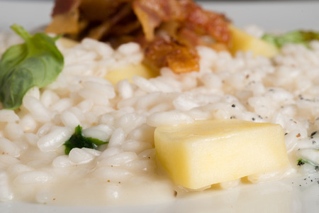 risotto with bacon apple and basil on a white dish Stock Photo