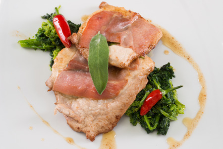 pork loin on a white dish with vegetables and chili pepper