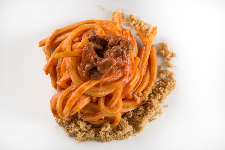 bolognese sauce pasta on white dish and wooden background