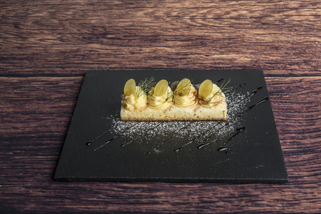 soft pie with custard and grapes on slate square dish Stock Photo