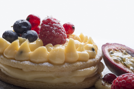 cake with cream , raspberries, mango, blueberries, and currants Stock Photo