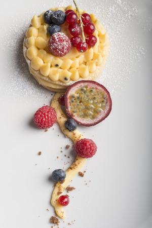 cake with cream , raspberries, mango, blueberries, and currants Stock Photo