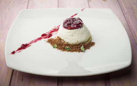 panna cotta with cherries marmalade cocoa and mint and biscuit Stock Photo