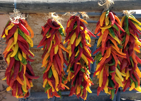 Various colors of chili hanging and drying outdoors.