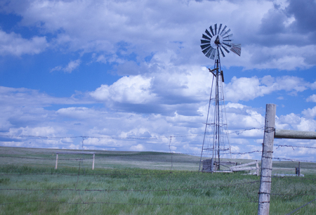 Windmill on the prairie with stormy skies in wide open spaces on a summer day