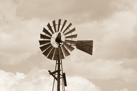 Sepia tone windmill with partly cloudy skies on a ranch on a warm summer day. Stock Photo