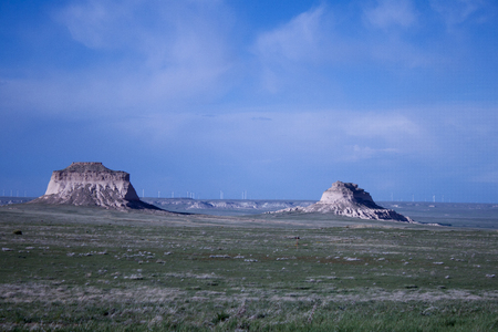Two Buttes in the mid-ground with a wind farm in the background, and wide open spaces and blue sky and sunshine on a summer day.