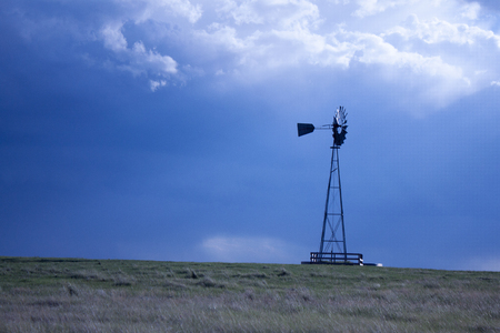 cielos abiertos: Windmill on the prairie with stormy skies in wide open spaces on a summer day