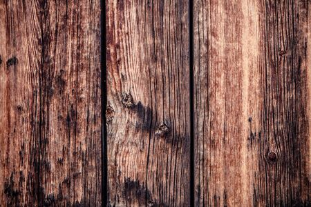 Old rustic barn wood texture or background has natural brown, tan, orange and yellow tones and would make a great background or texture.  It depicts mood and aging wood in a rustic environment.