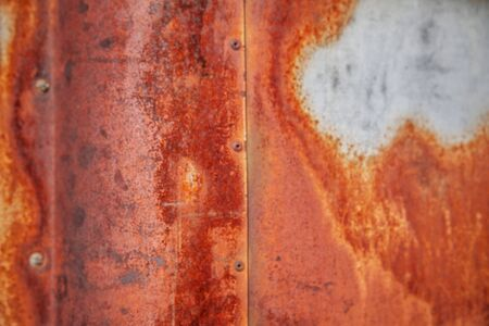 Old metal car door weathered, rusty and nearly paintless, showing multicolor patina patterns of rust, orange, brown ivory and purple. This is perfect for a background or texture or overlay. Stock Photo