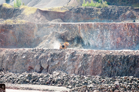 earthmover: earthmover is driving around in surface mine quarry. rocks. mining industry. Stock Photo