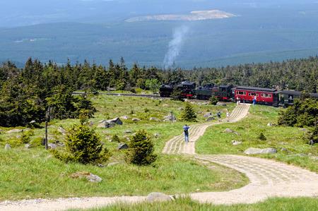 BROCKEN MOUNTAIN, SAXONY-ANHALT / GERMANY May 26 2012: historical locomotive is going up high to Brocken peak with tourists. Brocken is part of Harz National Park.