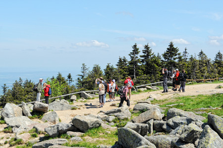 wonderfull: BROCKEN MOUNTAIN, SAXONY-ANHALT  GERMANY May 26 2012: People visiting Brocken Mountain National Park at resin (Germany). In front a group of people hiking walking around on peak. in background a wonderfull view over the resin mountain area.