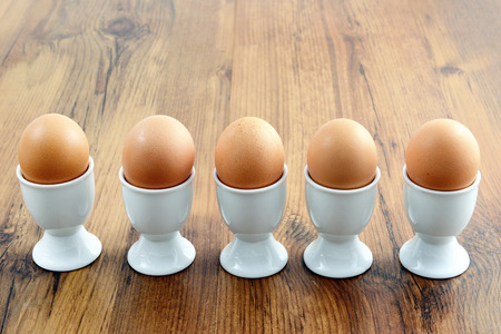 egg cups: five egg cups with natural brown eggs in a row on table