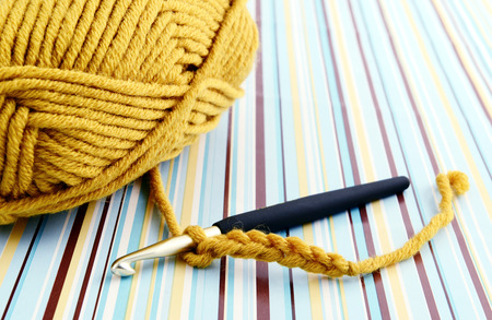 crocheting with brown wool. retro paper background. 스톡 콘텐츠