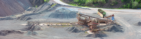open pit: panoramic images of a stone crusher machine in an open pit mine. mining industry. images created of 5 seperate images. Stock Photo