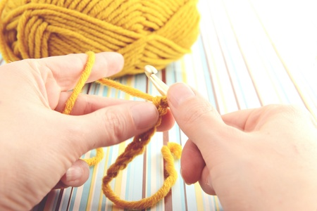 ball of wool: crocheting with wool ball and crocheting hook.