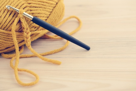 wool ball: crocheting with wool ball and crocheting hook. wooden table background