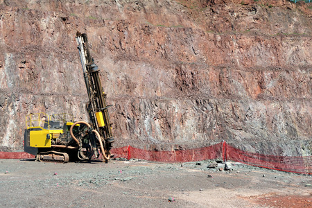 blasting: Driller in an open pit mine. porphyry rock material.