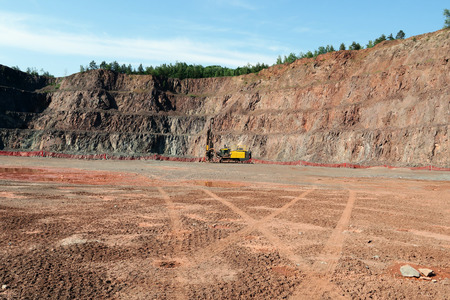 open pit: Driller in an open pit mine. porphyry rock material.
