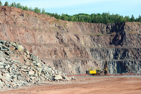 driller: Driller in an open pit mine. porphyry rock material.
