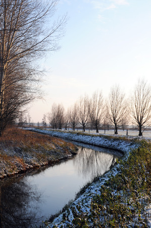 small river in wintertime at Havelland (Brandenburg, Germany). Along a path growing willow tries.