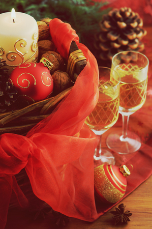 gold table cloth: basket with christmas decoration and two champagne glasses. Stock Photo