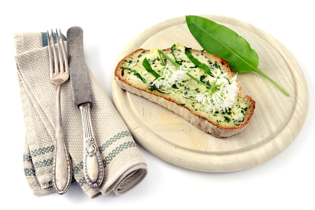bunch of wild garlic (ramson) and bread slice with ramson butter and antique silverware on isolated white background