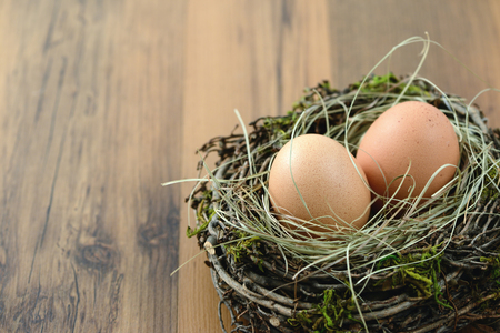 natural beige eggs on wooden table background.