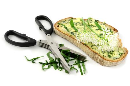 herb scissors with wild garlic butter bread slice on white background. breakfast. Stock Photo