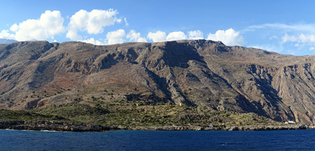 panoramic image of Crete (Greece) mountains of Libyan Sea side. driving with a boat along from Samaria gorge towards Loutro village. made of 4 images. Stock Photo