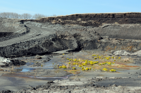 view into a coal mine with its dirt pond. mining industry.
