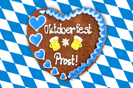Oktoberfest Gingerbread heart with bavarian white blue flag background. german word Prost (Cheerz)