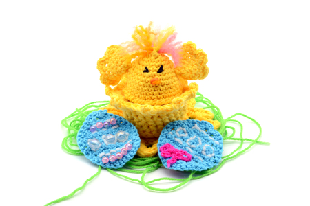 crochet Easter egg cup in chicken shape with easter eggs and greeen wool grass. white isolated background