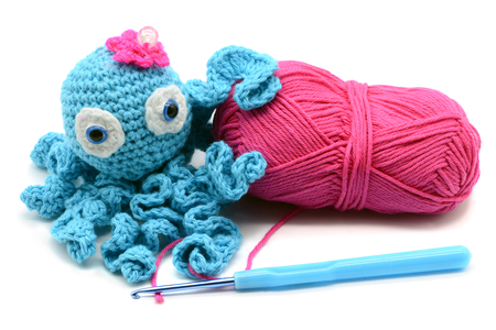 crocheted octopus of wool with woolball and crochet hook on white isolated  background Archivio Fotografico