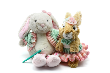 two Easter rabbits with crochet clothes on white isolated  background.