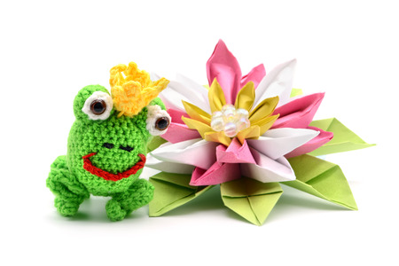 crochet frog king fairytale with crown and origami water lily on white background. tinker.