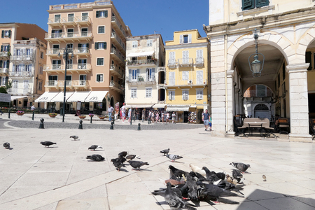 Corfu City, Corfu/ GREECE June 01 2018: Cityscape of Corfu town (Kerkyra). doves seeking food in front. Background people walking through historical small streets with stores, bars and restaurants at the esplanade. Editorial