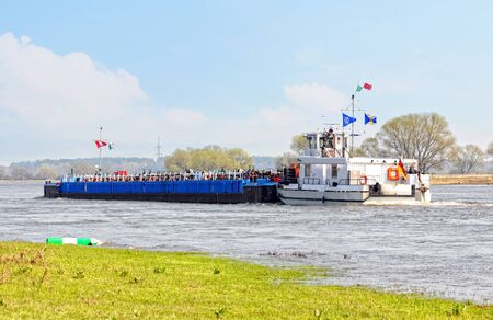 Barge at Elbe river. landscape in saxony anhalt (Germany). Willow trees and meadows.