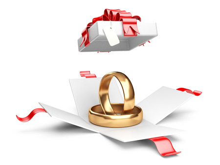 Opened gift box with golden rings isolated on a white background photo