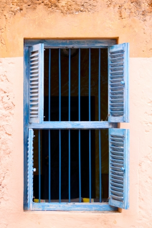 A front view of an old prison window with blue metal bars and open louvred blue shutters on a peach wall background photo