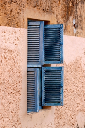 A perspective view of an old prison window with open louvred blue shutters on a peach wall background photo