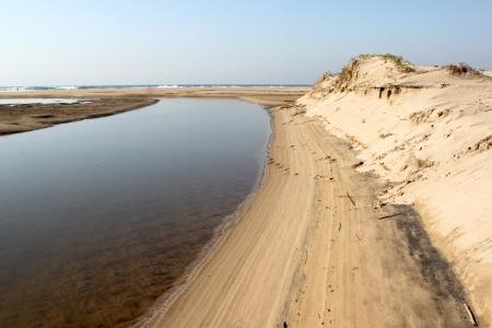 linea de flotaci�n: Una entrada de la laguna hacia el mar durante la marea baja que muestra la l�nea de flotaci�n, rodeado de dunas de arena