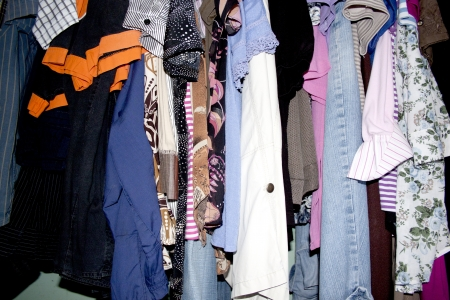 cluttered: A closeup of an assortment of secondhand cloting in a crammed messy wardrobe
