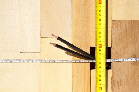 A pile of various size blocks of wood  with two tape measures and two pencils photo