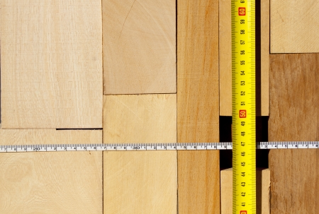 A pile of various size blocks of wood  with two tape measures photo