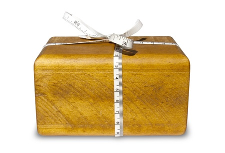 A block of wood with a tape measure tied around it resembling a gift on an isolated white background photo